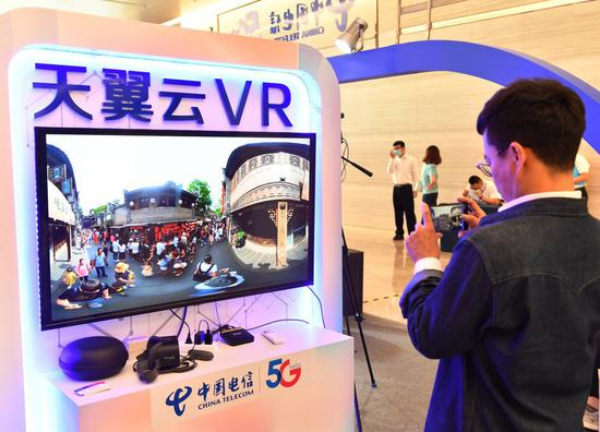 A visitor tries an intelligent exhibit at the 2020 Global Key and Core Technology Innovation Conference in Xi'an, northwest China's Shaanxi Province, Sept. 16, 2020. (Xinhua/Zhang Bowen)