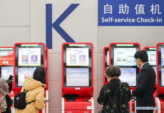 Passengers perform self-service check-in process at Terminal 2 building of the Shanghai Pudong International Airport in east China's Shanghai, Nov. 24, 2020. The airport's recent daily throughput maintains at around 1,000 flights, with passengers wearing face masks and orderly moving in and out. (Xinhua/Ding Ting)