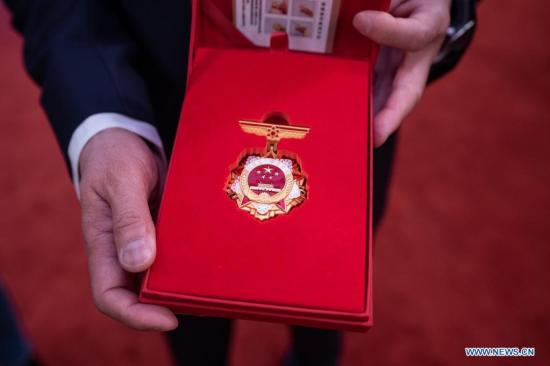An attendee shows the national labor award medal at a mobilization meeting marking the upcoming Labor Day in Beijing, capital of China, April 27, 2021. A mobilization meeting was held in Beijing on Tuesday to mark the upcoming Labor Day. Exemplary units and workers were granted national labor awards and honorary titles at the meeting. (Xinhua/Cai Yang)