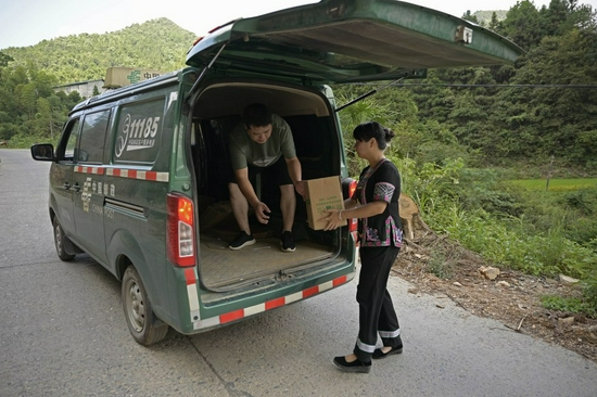 Shi Qiushi (R), a primary school teacher, brings ginger onto delivery vehicle in Longcheng Town of Tongdao Dong Autonomous County, central China's Hunan Province, Aug. 28, 2019. (Xinhua/Li Ga)